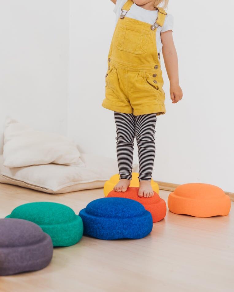 Meisje dat speelt met de gekleurde balansstenen van Stapelstein