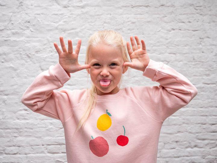 Blond miesje met haar handen naast haar oren en de tong uit de mond.