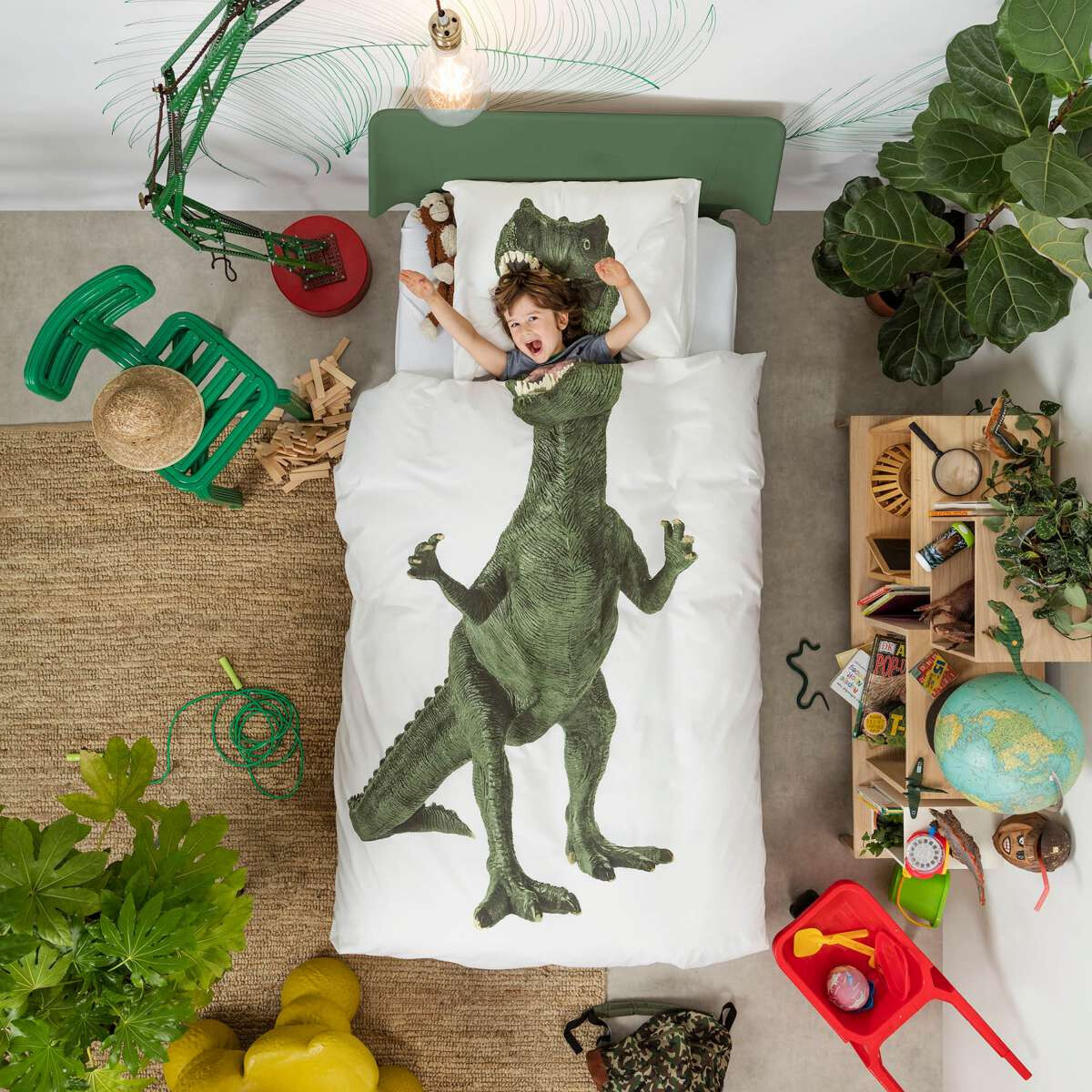 Kindje in bed onder een Snurk dekbedovertrek met dinosaurus tekening.