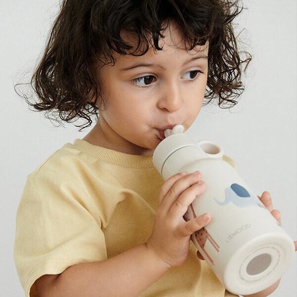 Kindje dat drinkt uit een drinkfles van Liewood