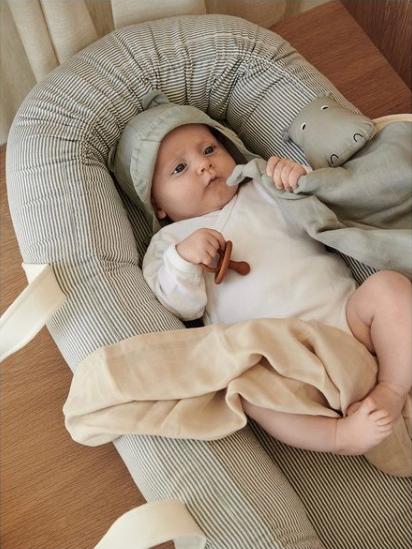 Babynestje Gro van Liewood met baby erin ingestopt met een swaddle