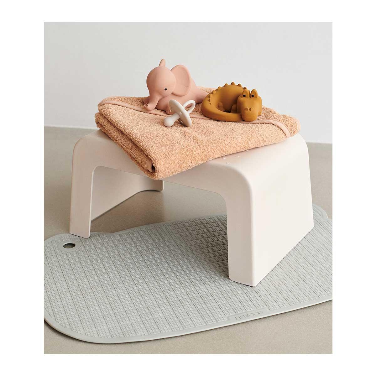 Liewood rubberen badspeelgoed en een katoenen badcape op een opstapje in cremekleur